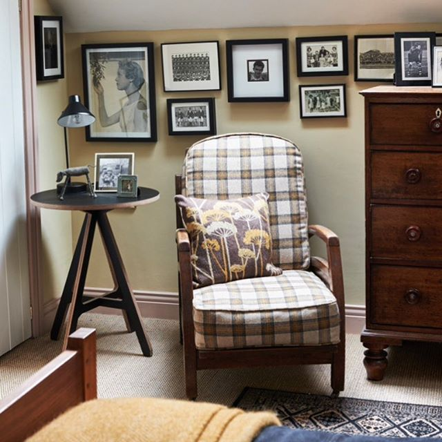 Cosy corner in a master bedroom. A gallery of family photos hang behind a reupholstered 1930's chair in Abraham Moon wool fabric. Side table from Byalex and classic habitat lamp. Walls in Farrow and Ball Cream. Sisal flooring and traditional wool rugs. #bedroom #bedroomdecor #sidetable #interior #interiordecor #interiorstyling #cosy #bedroomdesign