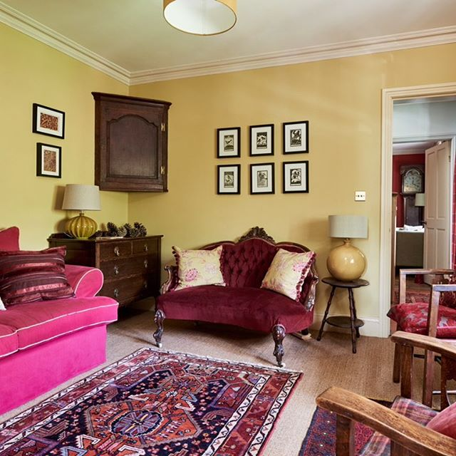 Colourful sitting room painted in a lovely mustard hue, P&P Library Tile V, sofas in dark red and pink. Sisal flooring and beautiful hand tufted rug. #interiordesign #interior #interiordecor #livingroom #livingroomdecor #sofa #rug #interiorstyling