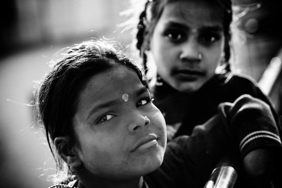 The girl in the previous photograph and her friend -- also an Aarti plate saleswoman. Children are often tasked with the job of selling Aarti plates to tourists. They wonder the ghats -- steps leading down to the Ganges -- with trays of Aarti plates, which Hindus release as oblations in the Ganges.