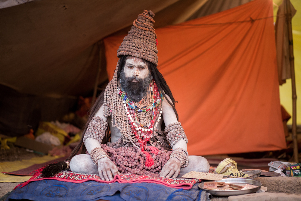 A sadhu, covered with garlands, shows that he is available or darshan by sitting at the edge of his tent, donation pan at foot.