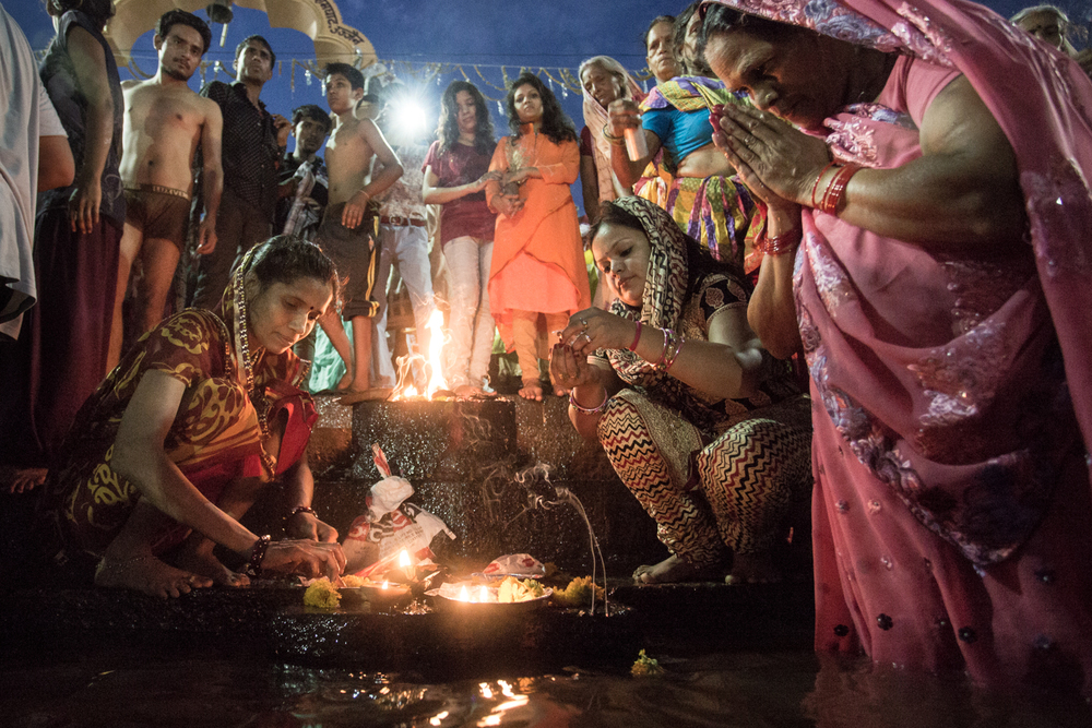 Women performing a fire puja on the banks of the Shipra.