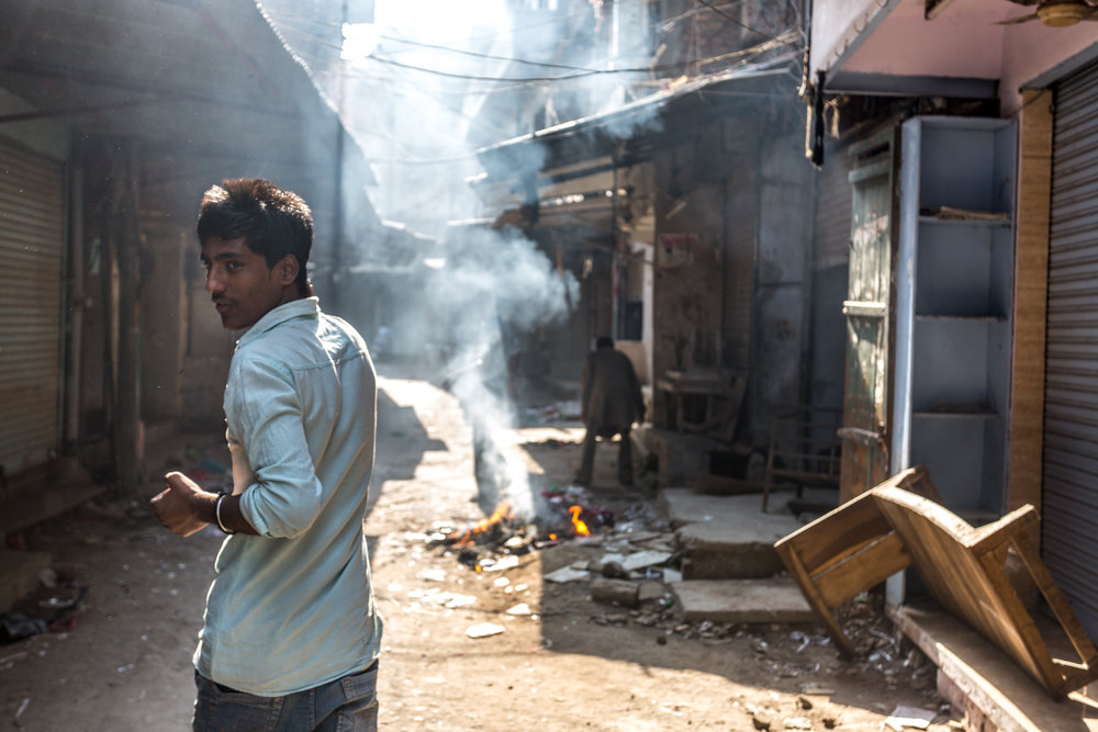 Surrounding the Harmandir Sahib complex is gritty capillary network of narrow market streets. In this picture, a young man walks past burning trash on a Monday, the day of the week when many stores close.