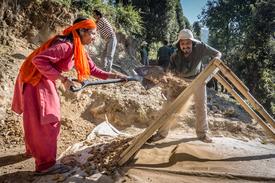 Dharmalaya groundskeeper, Pushkpa Thakur, and Sohan Tari, an Indian architecture student, filtering dirt into fine silt for for plaster.