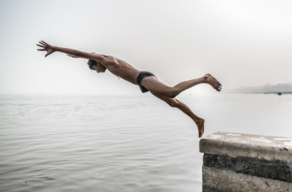 Boy jumping into the Ganges.