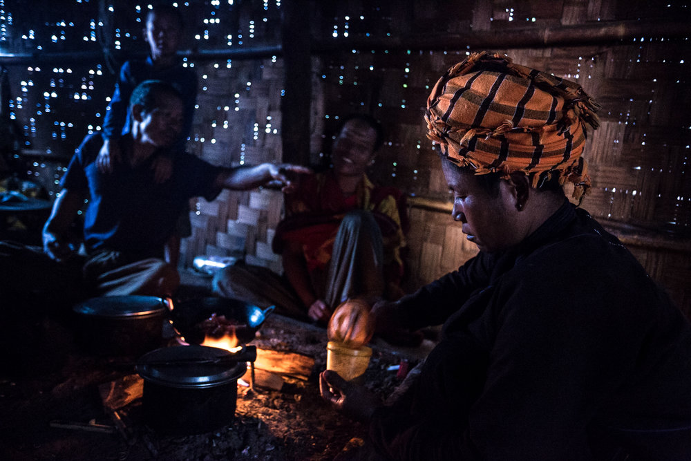 A women preparing dinner for her family. The villagers of Kyaut Su live in thatch houses.