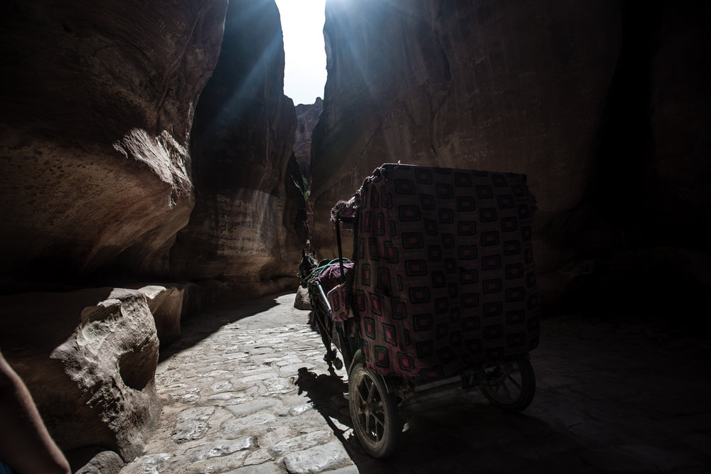 A bedouin horse-buggy carts tourists through the Siq's narrow corridor.