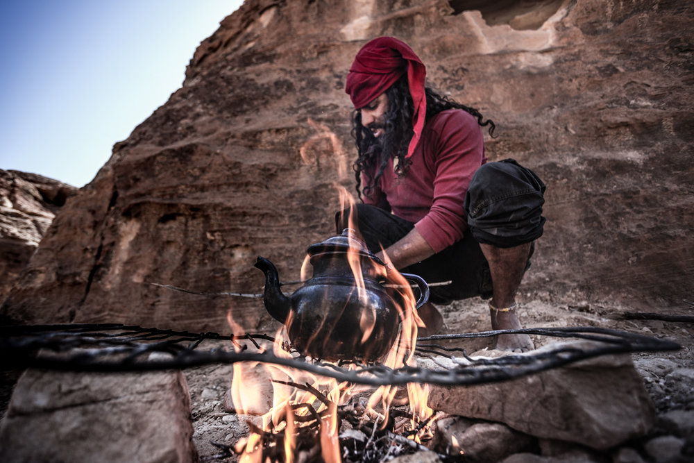"Faraj, a 22-year old Bedouin and native of Petra, Jordan, preparing ""Bedouin Whiskey"" (aka black tea with LOTS of sugar). Faraj also goes by ""Lost,"" a moniker given to him by his mother when, as a boy, he got lost while shepherding goats. Faraj survived the week alone in the desert by drinking goats milk. My first visit to Petra was in the summer of 2007, when I went with my dad and uncle. While the ancient ruins and scenery remained the same, visiting with a pretty, lively Australian girl provided a different experience that going with my two older male relatives. As soon as we appeared on the scene, a cohort of young bedouin guys readily suspended their activities of peddling camel rides and mule tours, and offered to show us Bedouin shortcuts to popular sites. We ended up spending the entire day being escorted around Petra by various Bedouin guys, Faraj among them. These young men, with flowing hair and outfitted in their tribe's traditional getup of red bandanas, black eyeshadow, seemed more like Jack Sparrow stunt doubles than of the Nabatean pedigree claimed by the Bedouins in the area. It was hard not to like the affable characters who wielded preternatural smiles stained with years of drinking ""Bedouin whiskey"" (what they enjoy calling tea in front of foreigners).  From them, Bianca and I learned about the in and outs of Bedouin life and the expressively deep-seated connection Bedouins of the area have with Petra. They were also particular fond of telling Bianca about the story of an Austrian women who had married a Bedouin man from their community, a story oft repeated throughout the day, invariably leading up to one of their favorite phrases to say in English: ""A man without a wife is like a kitchen without a knife."""