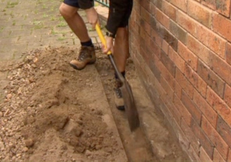 Digging a trench around the house before treating the soil