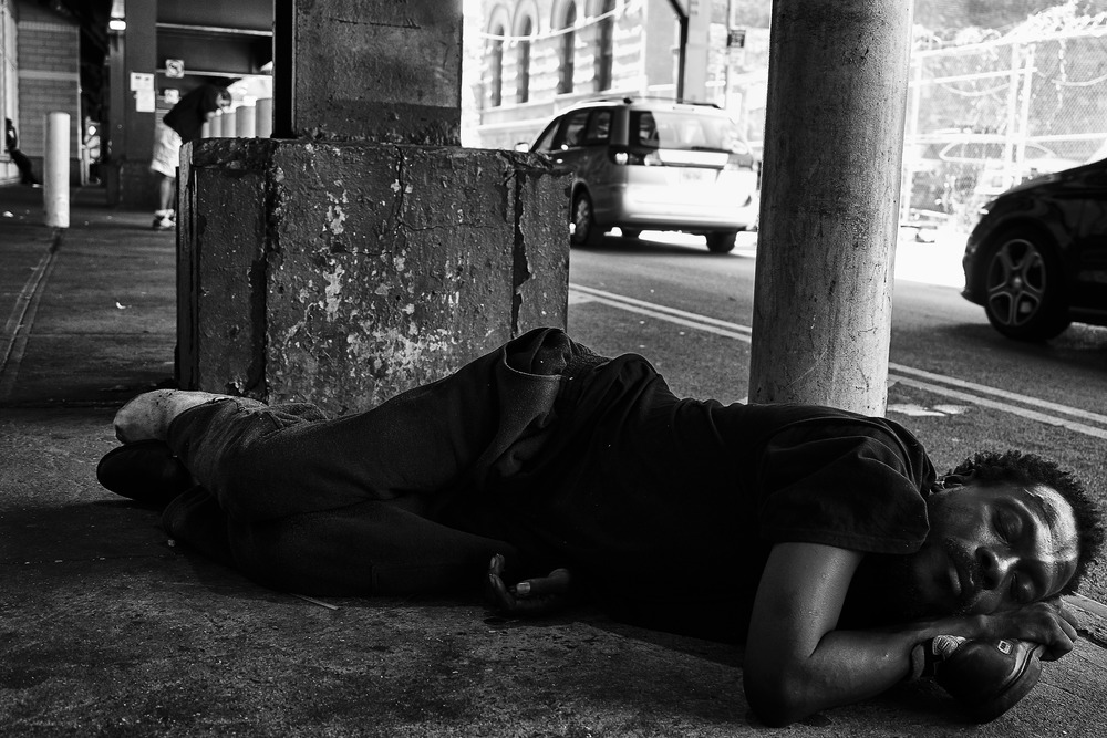 A homeless man sleeps on the pavement at 125th St. & Park Avenue on Thursday, September 17, 2015 in New York, N.Y.