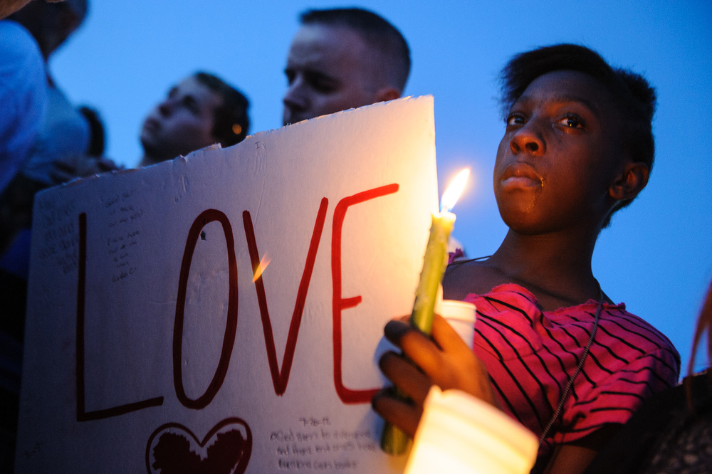 "Unique Bradley, 14, of Aurora, CO, joined other mourners who held a vigil at a nearby park(in the vicinity of 14701 East Exposition Avenue) in Aurora, CO, after a heavily armed gunman wearing a gas mask went on a real-life rampage at a midnight showing of the ""The Dark Knight Rises"" on July 20, 2012, killing 12 people and wounding 59 others."