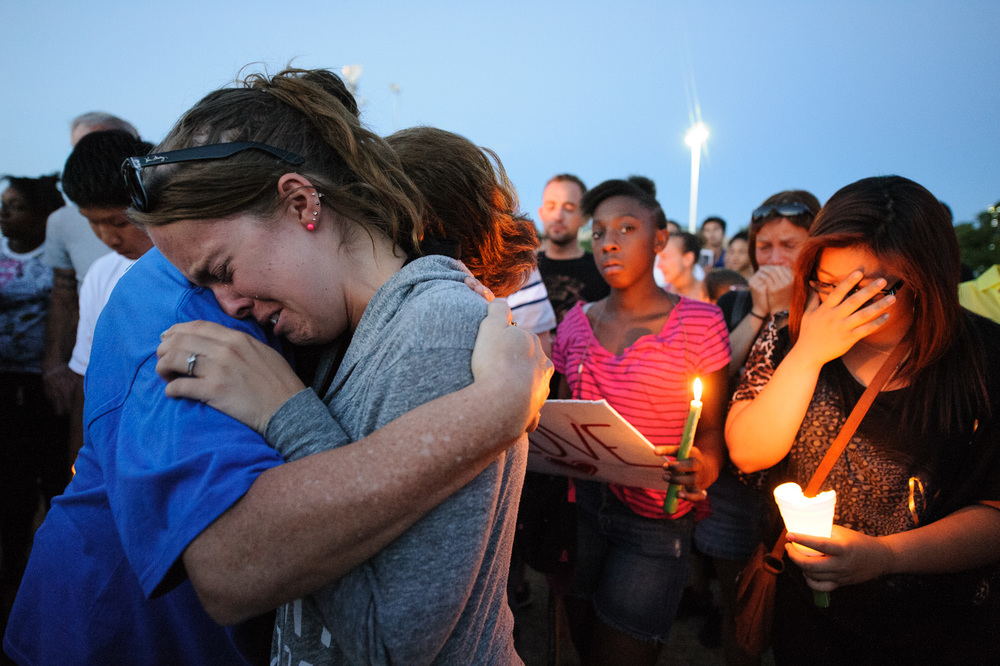 "Lindsey Revier, at left, of Aurora, CO, joined other mourners at a vigil after a heavily armed gunman went on a rampage at a midnight showing of the ""The Dark Knight Rises"" on July 20, 2012, killing 12 people and wounding 59 others."