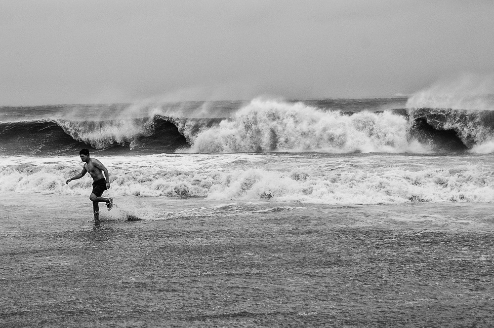 A man runs in the surf in Coney Island, Brooklyn, N.Y., as Hurricane Sandy approaches landfall on the East Coast on Monday, Oct. 29, 2012.