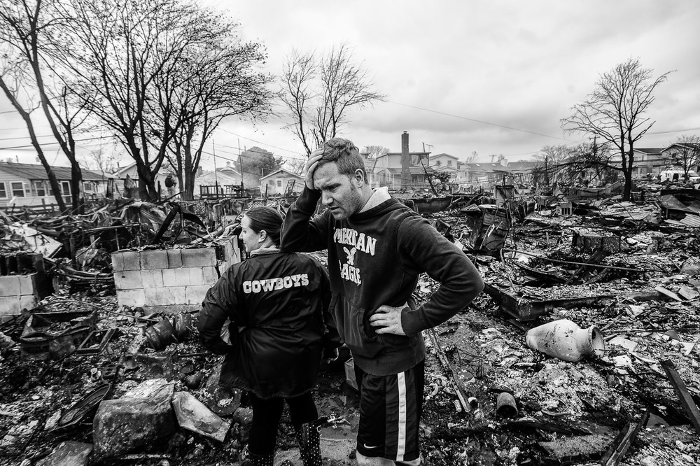 Danny Cook, right, surveys the damage to his parent's home after at least 80 flooded homes were destroyed in Breezy Point, Queens, after Hurricane Sandy touched down on the East Coast. At left is his cousin Eileen Kehoe.