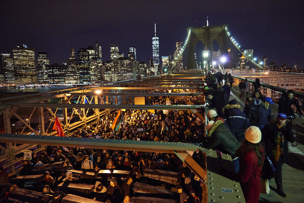 Demonstrators march across the Brooklyn Bridge carrying coffins marked with names of people killed by police during a protest following a Staten Island grand jury's decision not to indict the NYPD officer involved in the chokehold death of Eric Garner on Thursday, Dec. 4, 2014 in New York, N.Y.
