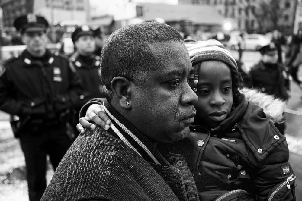 A former police officer and his daughter visit a memorial for New York Police Department officers Rafael Ramos and Wenjian Liu on Monday, Dec. 22, 2014 in Brooklyn, N.Y. The two officers were killed in their patrol car when Ismaaiyl Brinsley shot them to death in Brooklyn.