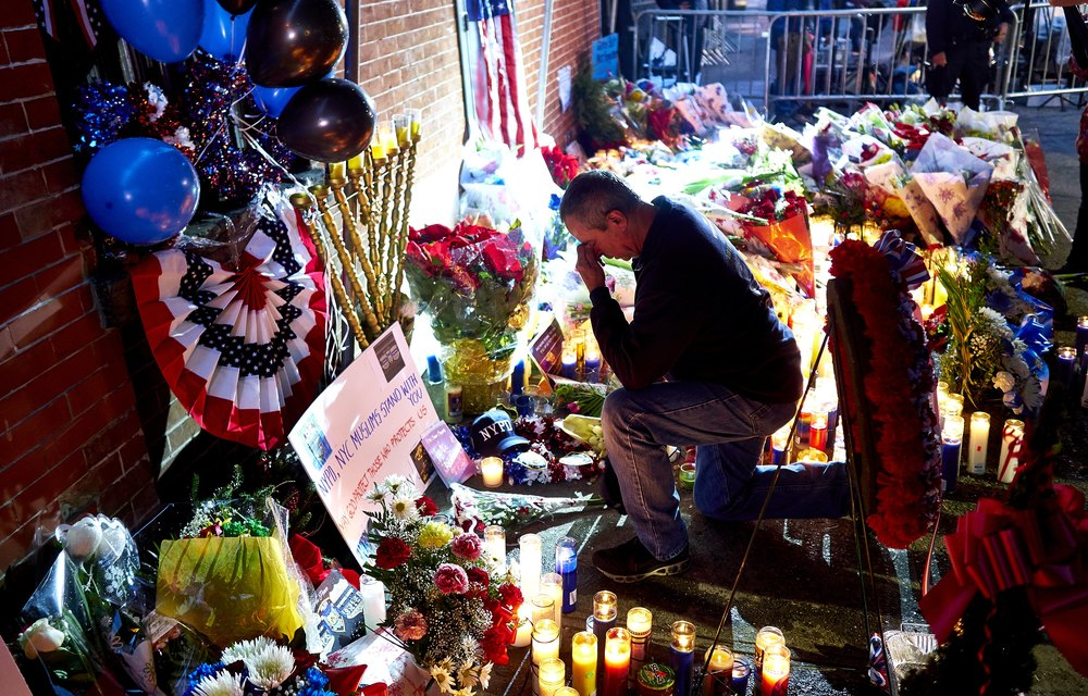 Retired Port Authority Police Officer Henry Lallave pauses at a memorial for New York Police Department officers Rafael Ramos and Wenjian Liu on Monday, Dec. 22, 2014 in Brooklyn, N.Y.