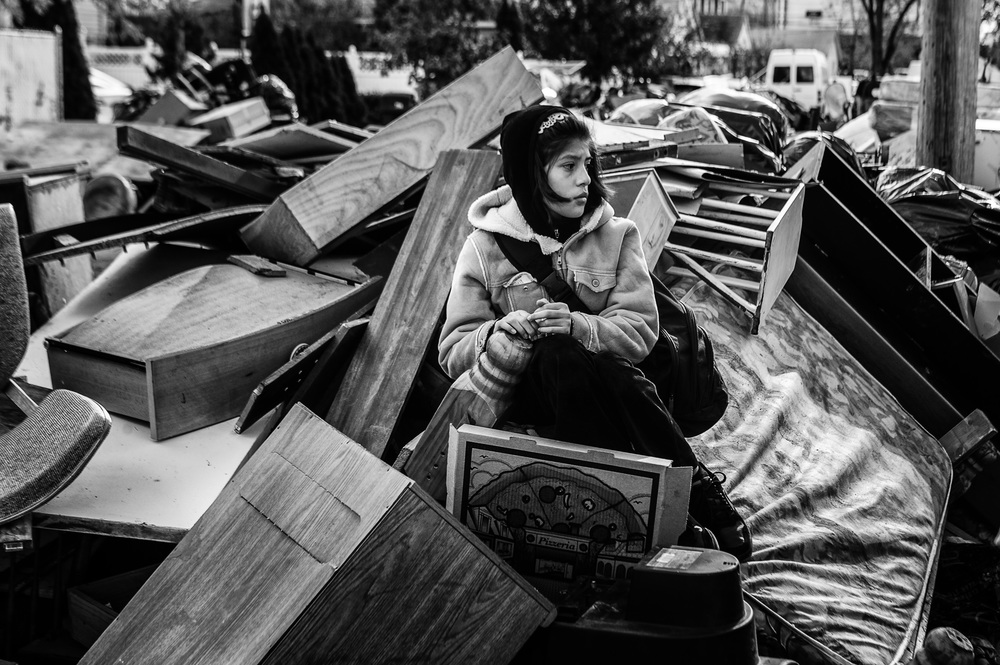 Michelle Cruz, 10, sits on a mound of destroyed furniture before she and her father left their Midland Beach, N.Y., home on Nov. 3, 2012.  Cruz and her family weathered Hurricane Sandy as rising surges almost submerged the attic they sought refuge in.