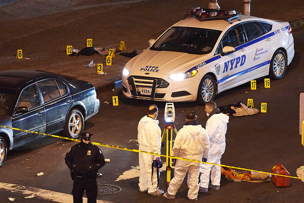 Crime scene technicians examine the squad car in which New York Police Department officers Rafael Ramos and Wenjian Liu were shot and killed in by Ismaaiyl Brinsley fired in Brooklyn, N.Y., on Saturday, Dec. 20, 2014.