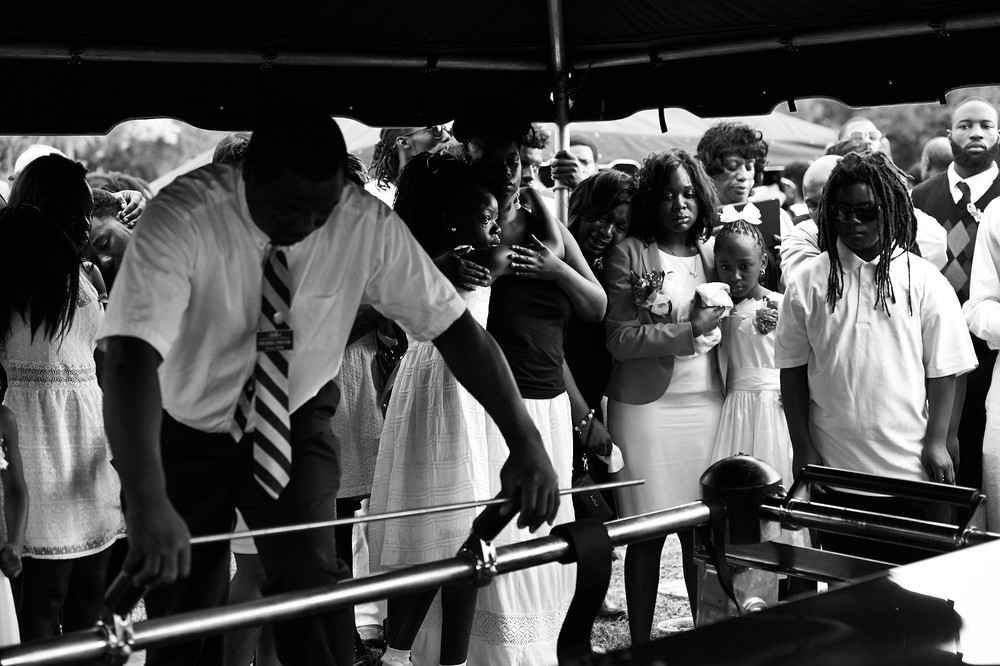 Family members and friends grieve by the casket of Tywanza Sanders during a burial service form Sanders and his aunt, Susie Jackson, at Emanuel AME Church Cemetery on Saturday, June 27, 2015 in Charleston, S.C. Sanders and Jackson were shot to death inside Mother Emanuel AME Church when gunman Dylann Roof opened fire during a Bible study session last week, killing nine.