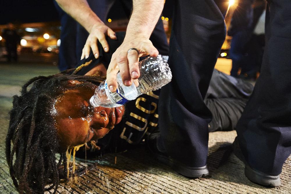 A protestor who confronted police officers after a curfew was in effect was pepper-sprayed and arrested on Saturday, May 2, 2015 in Baltimore, M.D.  Baltimore authorities, in a swift and sudden show of legal might, charged six police officers yesterday in connection with the death of Freddie Gray, who died in police custody after he was arrested last month.