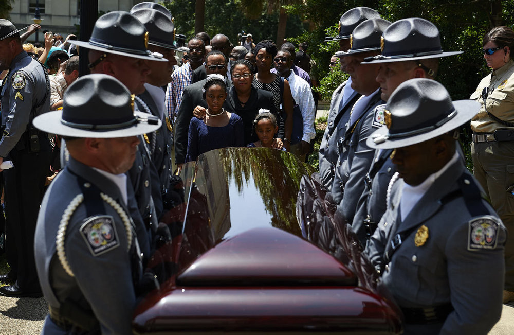 Jennifer Pinckney, center, and her daughters, Eliana, left, and Malana, follow the casket of Sen. Clementa Pinckney as it is carried into the South Carolina Capitol building to lie in repose on June 24, 2015 in Columbia, S.C. Sen. Pinckney, a church pastor, and eight others were shot to death inside Mother Emanuel AME Church when gunman Dylann Roof opened fire during a Bible study session.