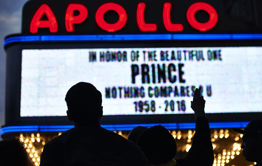 Fans gather outside the Apollo Theatre to pay tribute to musician Prince after his death on Thursday, April 21, 2016 in New York, N.Y. Prince, the multi-talented musical genius who emerged from Minneapolis with a unparalleled funk-rock sound that made him a global megastar, died suddenly at his home.