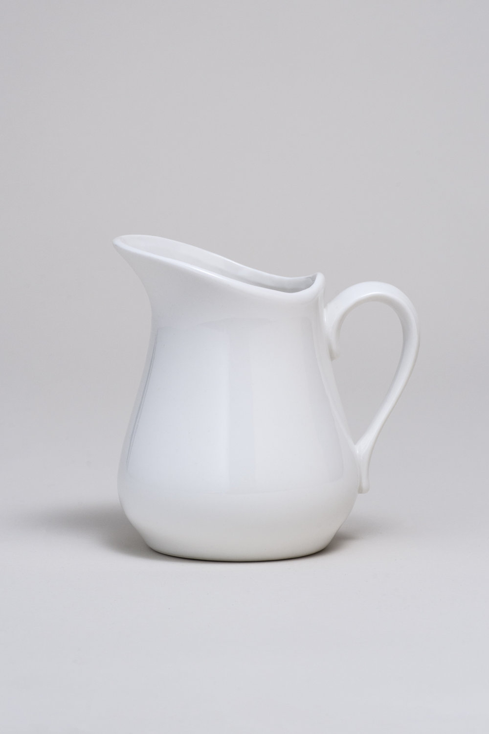 "Porcelain Pitcher 12 oz. Height 4 1/2""  Width 3 1/2""  Top opening 2 5/8""X3"" $2.00"
