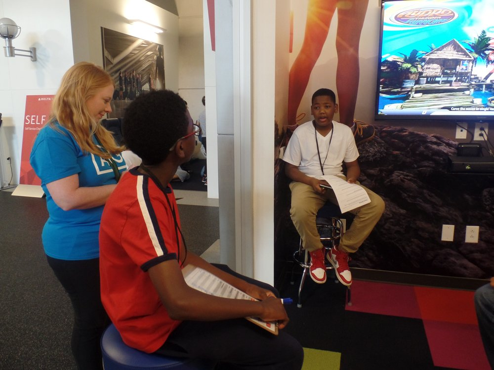AIG Volunteer talks with students in JA BizTown at the JA Chick-fil-A Foundation Discovery Center