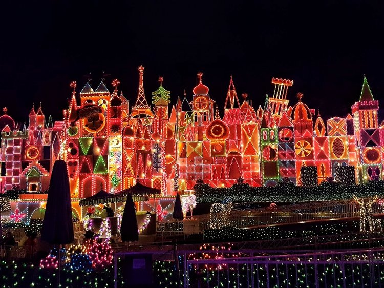 the facade of its a small world all lit up at night its beyond impressive - When Does Christmas Start At Disneyland