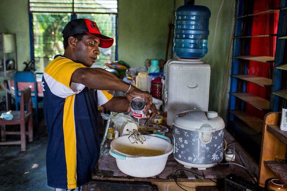 Sambil memasak kue bolu terkenal buatannya, Yosua menambahkan susu kental manis ke dalam adonan campuran kue.