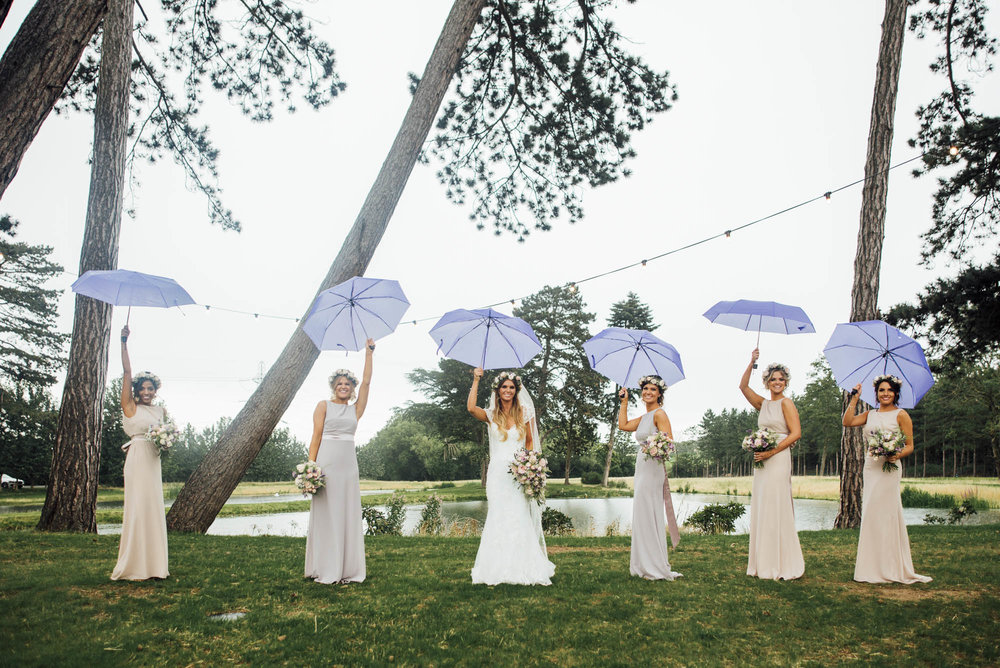Rainy day wedding in Hertfordshire  Gorgeous bridesmaids with purple umbrellas