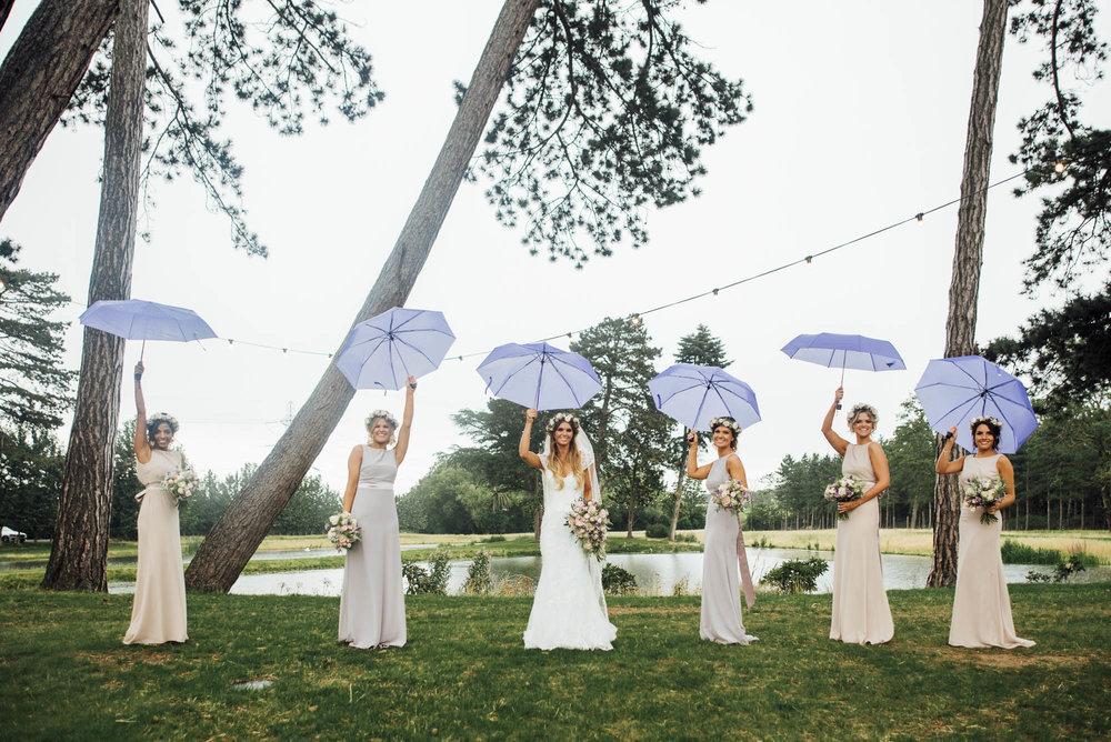 Rainy day wedding in Hertfordshire  Gorgeous bridesmaids with purple umbrellas