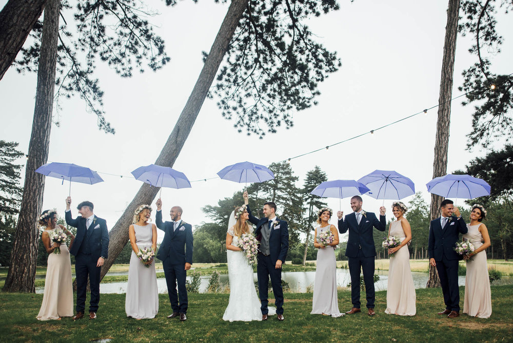 Ushers carry umbrellas for bridesmaids on a rainy wedding day in hertfordshire
