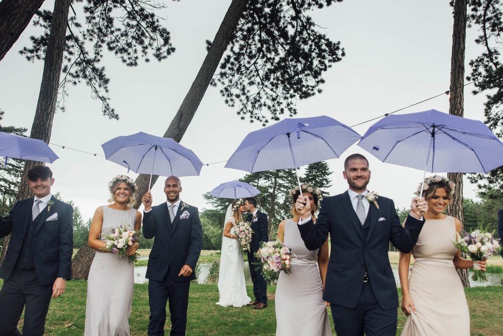 Bride & Grrom share a kiss as bridesmaids and ushers walk away - bridal group shot