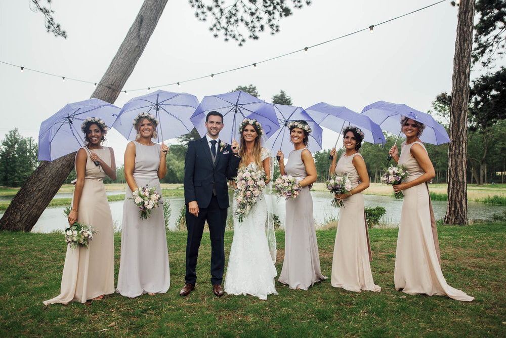 Bride & Groom with bridesmaids holding umbrellas on a rainy wedding day