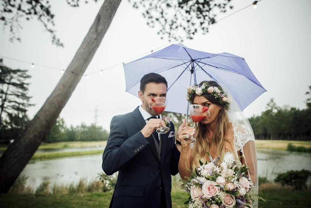 Bride & Groom share a cocktail under umbrellas on their rainy wedding day on Brook Farm Cuffley