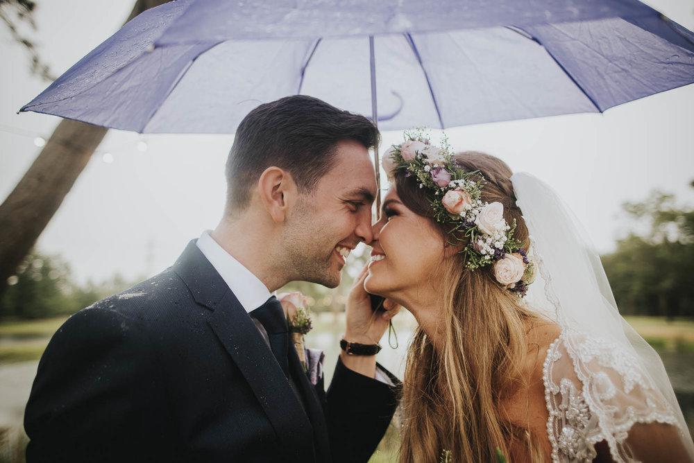Bride & Groom share a kiss under an umbrella on their rainy wedding day