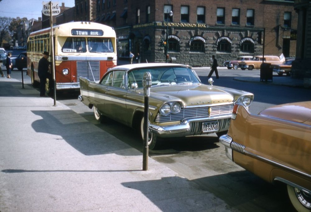The city of Sudbury, Ontario, claims the honour of having installed the country's first parking metres in August of 1940.  Town bus on Queen Street West at Main Street, Brampton, Ont., c.1960. Region of Peel Archives/Cecil Chinn Fonds.