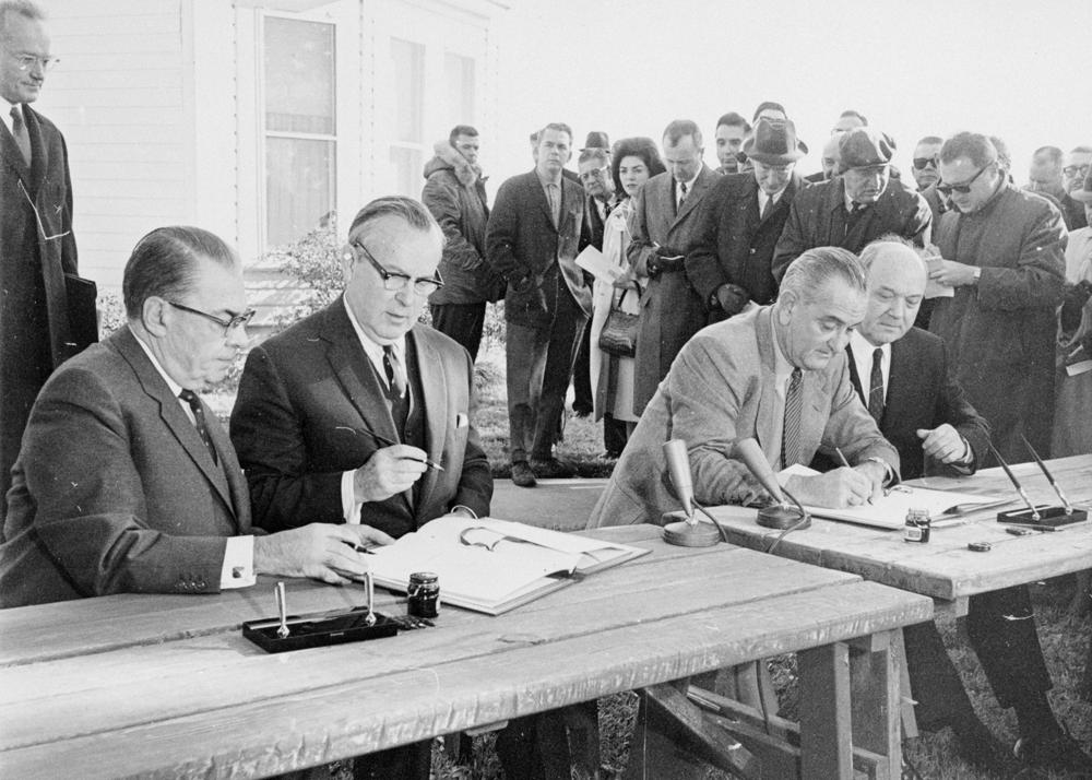 1965 年 1 月 15 日,在德克萨斯州约翰逊城的林顿·约翰逊农场签署《加拿大-美国汽 车贸易协定》。加拿大图书馆与档案馆,PA-139787。