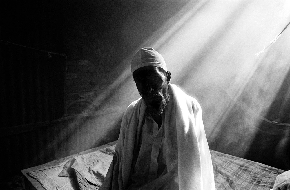 An ailing 75-year-old Urdu-speaking man sits alone in his room in Pat Godam Camp in Mymensingh, Bangladesh. He has no family left and does not have the resources to obtain health care.