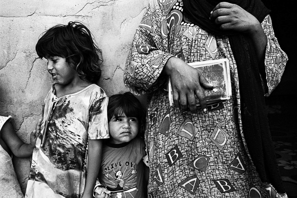 The Dom (gypsy) community are some of the most vulnerable people in Iraq. This 35-year-old woman holds her Iraqi nationality card and stands with her five and three-year-old daughters. None of her four children have documents. Many of the Dom throughout Iraq, were issued an Iraqi Nationality card with an special 'exception' stamp in it, which many authorities around the country now do not recognize as being legitimate.