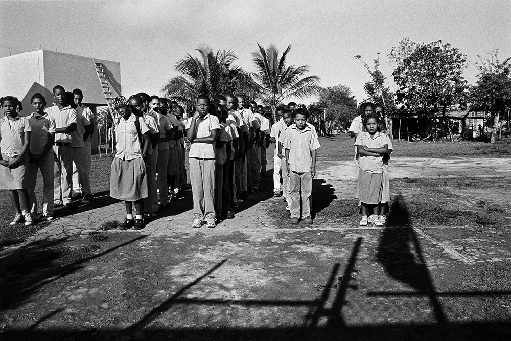 Children stand outside their school in a remote batey and recite the Dominican Pledge of Allegiance as the Dominican flag is raised before classes. Most will not be permitted to go to school past the 8th grade because most have been denied documentation based on their Haitian ethnicity, therefore will lack sufficient documentation to continue their studies.