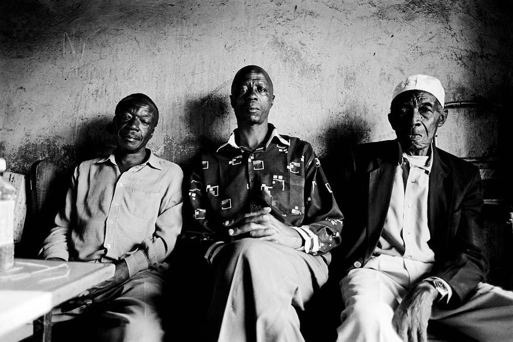 Three men from the Nubian community sit in a small shop in the Kibera slum.