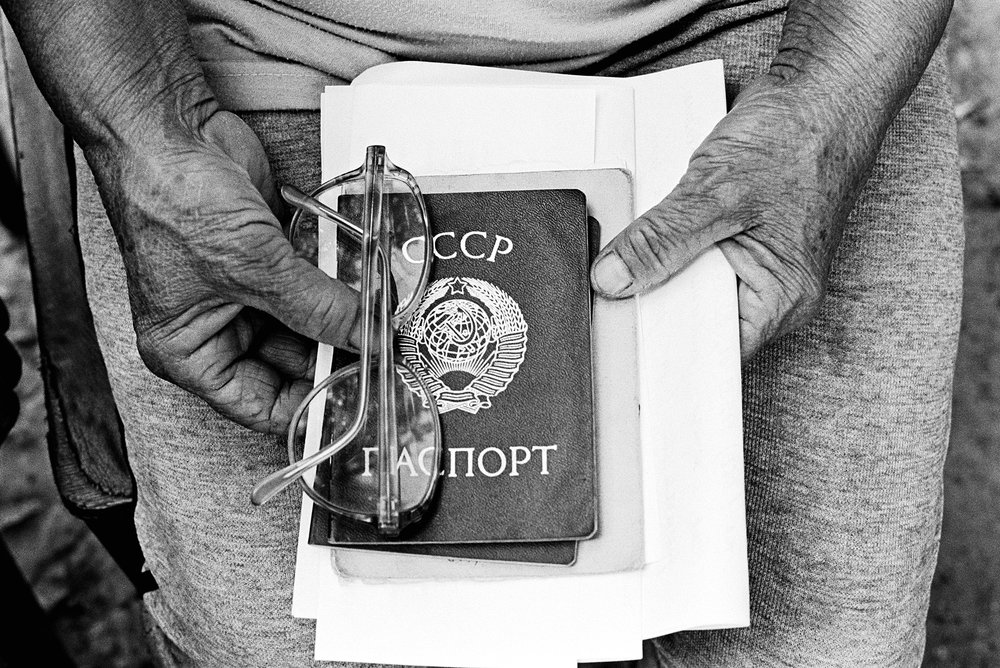 A stateless woman in eastern Ukraine holds her expired Soviet passport.