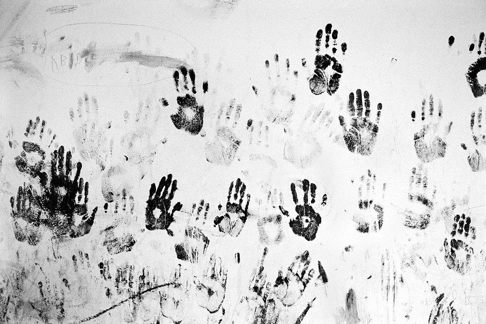 Handprints of Galjeel children decorate a wall of an abandoned school. Years ago Galjeel children went to school. Now most do not receive an education.