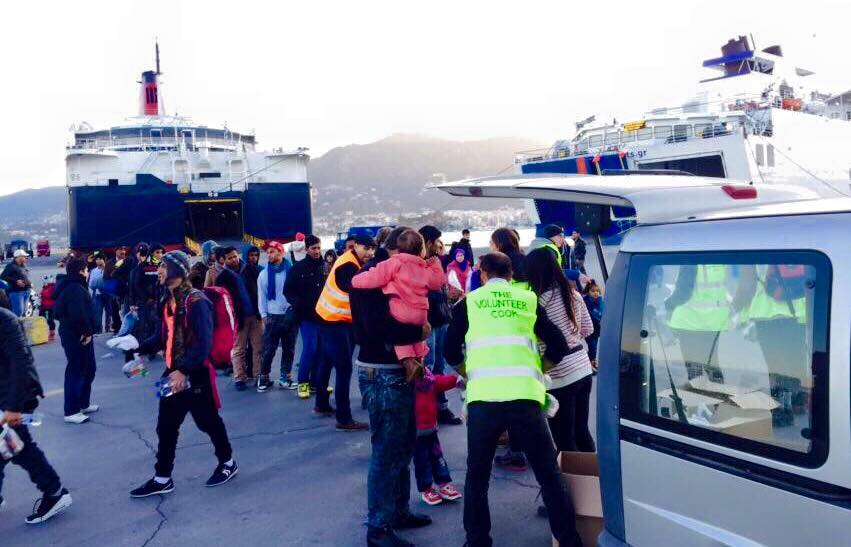 Volunteers hand out snack bags to refugees at Mytilini port, right before they board the ferry