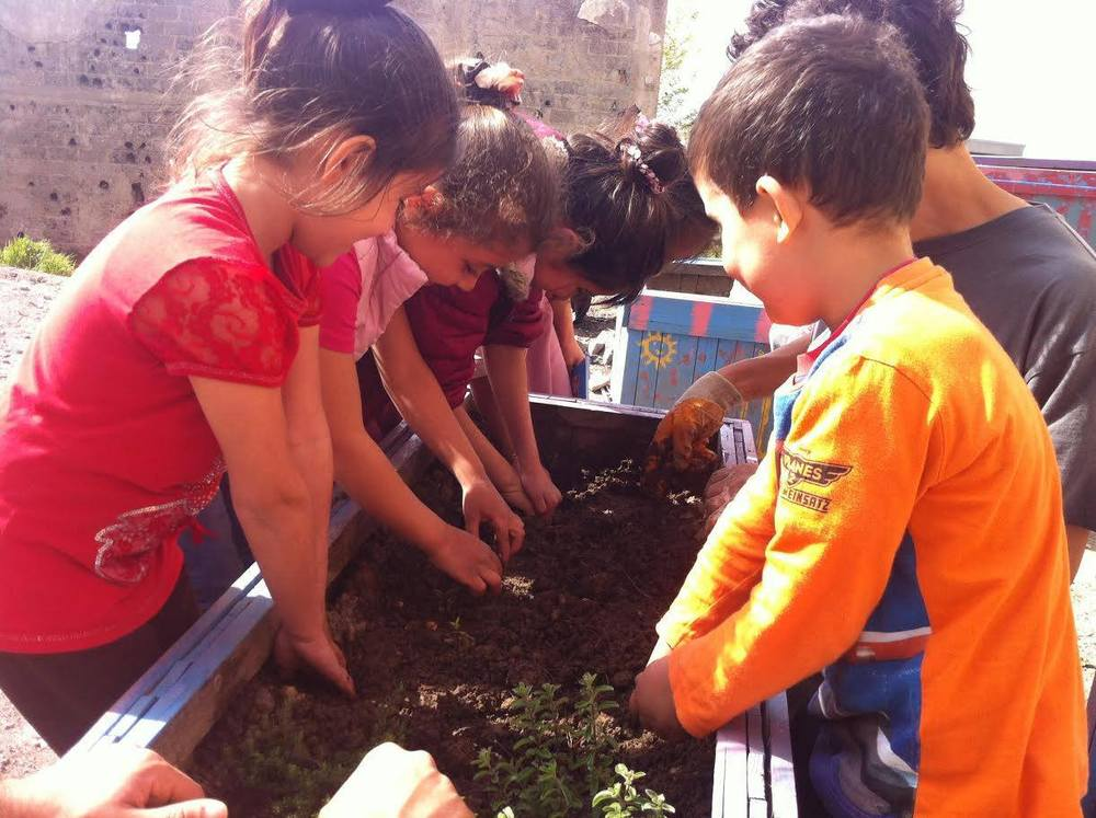 The children are helping plant a garden-box in the outside play area. Learning about plants and how things grow.