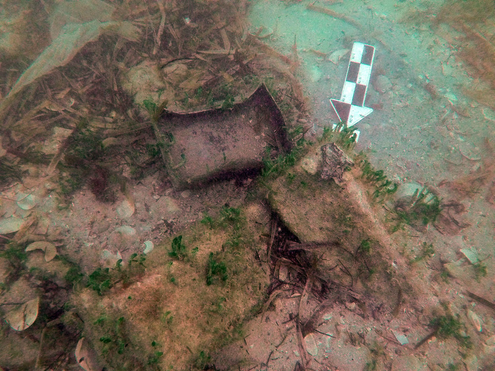 A lead box and lid amongst iron ballast blocks in the stern section of   Le Dragon