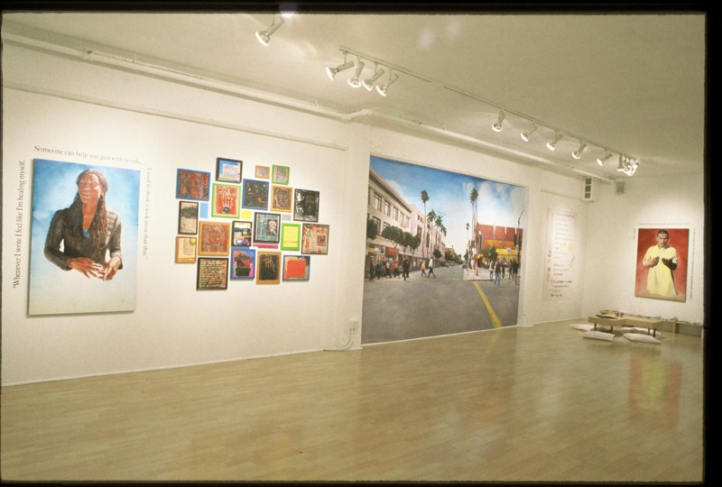 Installation view of the exhibit at Intersection for the Arts, with pieces created during a free workshop series and an original mural created for the space.