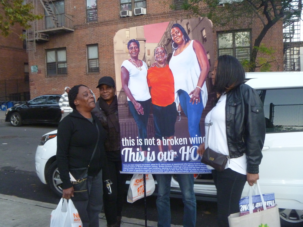 MJP members hold up a poster that we designed before it will be wheatpasted in the neighborhood/research area.